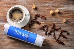 Composição com NOTÍCIA FALSIFICADA da frase e xícara de café na tabela de madeira imagens de stock royalty free