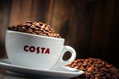 Composição com o copo do café e dos feijões de Costa Coffee Fotos de Stock Royalty Free