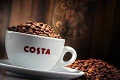 Composição com o copo do café e dos feijões de Costa Coffee Imagem de Stock