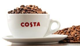 Composição com o copo do café e dos feijões de Costa Coffee Fotografia de Stock Royalty Free