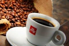 Composição com o copo do café e dos feijões de Illy Fotografia de Stock Royalty Free