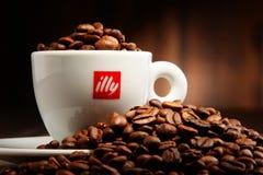 Composição com o copo do café e dos feijões de Illy Imagens de Stock Royalty Free