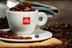 Composição com o copo do café e dos feijões de Illy Imagem de Stock