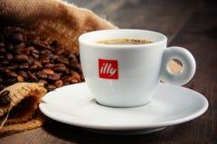 Composição com o copo do café e dos feijões de Illy Fotografia de Stock
