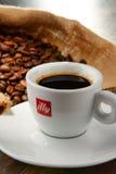 Composição com o copo do café e dos feijões de Illy Foto de Stock Royalty Free