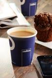 Composição com o copo do café e dos feijões de Lavazza Fotografia de Stock