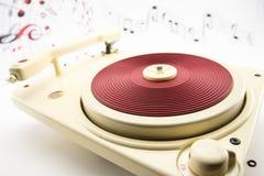 Composição com o jogador de registro vermelho do vintage e notas musicais Foto de Stock