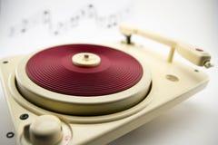 Composição com o jogador de registro vermelho do vintage e notas musicais Foto de Stock Royalty Free