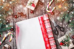 A composição com o xmas que envolve, abeto do Natal ramifica, presentes, cones do pinho, decorações vermelhas no fundo de madeira imagens de stock royalty free