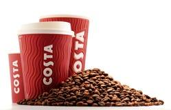 Composição com os copos do café e dos feijões de Costa Coffee Fotos de Stock