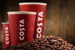 Composição com os copos do café e dos feijões de Costa Coffee Foto de Stock