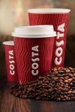 Composição com os copos do café e dos feijões de Costa Coffee Fotografia de Stock