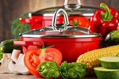 Composição com os potenciômetros de aço vermelhos e a variedade de legumes frescos Imagens de Stock Royalty Free