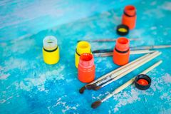 Composição com pinturas acrílicas ou as escovas amarelas e alaranjadas do óleo e no fundo ciano do grunge foto de stock royalty free