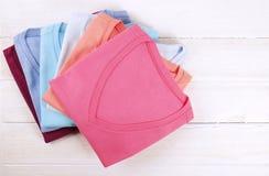 Composição com a roupa dobrada, unisex para o homem e a mulher, cor diferente & material Pilha da lavanderia, roupa limpa seca Fotos de Stock