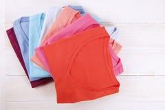 Composição com a roupa dobrada, unisex para o homem e a mulher, cor diferente & material Pilha da lavanderia, roupa limpa seca Imagem de Stock