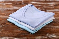 Composição com a roupa dobrada, unisex para o homem e a mulher, cor diferente & material Pilha da lavanderia, roupa limpa seca Imagens de Stock