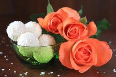 Composição com três rosas e doces no fundo escuro imagem de stock