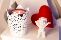 Composição com um anjo, uma vela e um coração vermelho Imagem de Stock