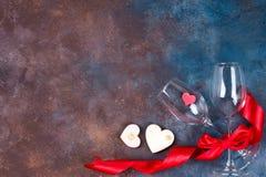 Composição com vidros de vinho, fita e corações decorativos no fundo de pedra com espaço da cópia, configuração lisa imagens de stock