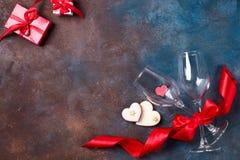 Composição com vidros de vinho, fita e corações decorativos no fundo de pedra com espaço da cópia, configuração lisa imagem de stock