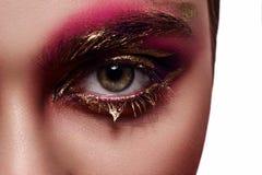 Composição cor-de-rosa e dourada no olho da mulher foto de stock