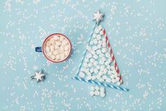 Composição criativa com o copo da árvore quente do cacau ou do chocolate e de abeto feita do marshmallow no fundo azul dos confet Imagens de Stock Royalty Free