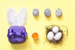 Composição criativa de easter com ovos pintados, caixa violeta e ninho, no fundo amarelo Configuração lisa fotografia de stock royalty free