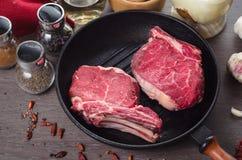 Composição crua do bife do olho do reforço da carne fresca na bandeja da grade no fundo de madeira Fotos de Stock Royalty Free