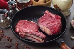 Composição crua do bife do olho do reforço da carne fresca na bandeja da grade no fundo de madeira Imagem de Stock Royalty Free