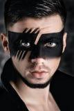 Composição da arte da fantasia homem com máscara pintada preto na cara Feche acima do retrato Composição profissional da forma fotografia de stock royalty free