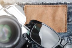 composição da câmera de SLR do vintage e óculos de sol em calças de brim gastas em torno da placa de couro vazia - conceito do cu fotografia de stock royalty free