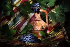 Composição da embarcação da água do Uzbeque e de uvas para vinho tradicionais Foto de Stock Royalty Free