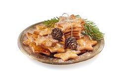 A composição da estrela deu forma a cookies do gengibre e a cones do pinho no prato velho do metal sobre o fundo branco foto de stock