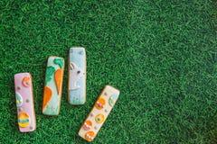 A composição da Páscoa com cookies de easter pintou varas no fundo da grama verde Conceito da Páscoa com espaço da cópia Configur fotografia de stock