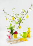 A composição da Páscoa da cor da sua suspensão do vidoeiro ramifica com folhas, dois coelhos e cuidado para o jardim fotos de stock royalty free