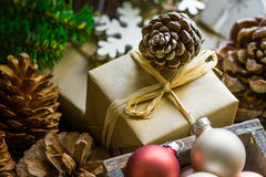 Composição da pilha de caixas de presente no papel do ofício, bolas coloridas do Natal e do ano novo, cones do pinho, ramos de ár Imagens de Stock