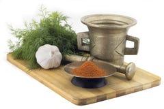 A composição das especiarias, mistura pimentos secos, aneto, alho, moedor da especiaria do vintage isolado no fundo branco Fotografia de Stock