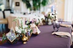 A composição das flores nos florariums que estão na tabela cobriu b Foto de Stock