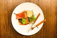 A composição de alimento da carne no sangue decorada com verdes e colocada na placa branca perto do kitchenware Imagens de Stock Royalty Free