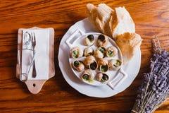 A composição de alimento dos shell e do pão do caracol cercados por flores e pela cutelaria roxas secadas Acima da vista Fotografia de Stock Royalty Free