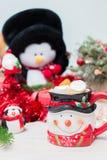 A composição de ano novo na tabela com a decoração, a caneca e um pulso de disparo vermelho imagens de stock