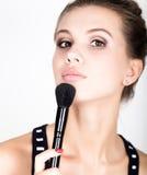Composição de aplicação modelo fêmea em sua cara Jovem mulher bonita que aplica a fundação em sua cara com uma escova compor Foto de Stock Royalty Free
