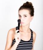 Composição de aplicação modelo fêmea em sua cara Jovem mulher bonita que aplica a fundação em sua cara com uma escova compor Imagens de Stock