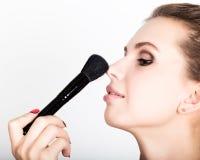 Composição de aplicação modelo fêmea em sua cara Jovem mulher bonita que aplica a fundação em sua cara com uma escova compor Fotografia de Stock