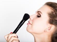 Composição de aplicação modelo fêmea em sua cara Jovem mulher bonita que aplica a fundação em sua cara com uma escova compor Fotos de Stock Royalty Free