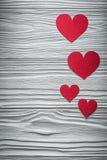 Composição de corações vermelhos em cartões do Valentim da placa de madeira Fotos de Stock