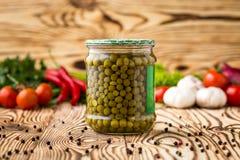 Composição de ervilhas verdes conservadas no frasco e nos ingredientes na madeira fotografia de stock royalty free
