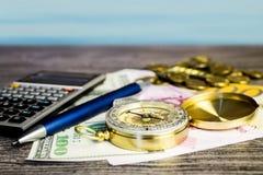 Composição de um compasso, de cédulas, de moedas, de calculadora e de pena do turista no fundo do mar Fotografia de Stock