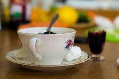 A composição de um copo da porcelana, de pires e de um vidro encheu-se com o doce de fruta fotografia de stock royalty free